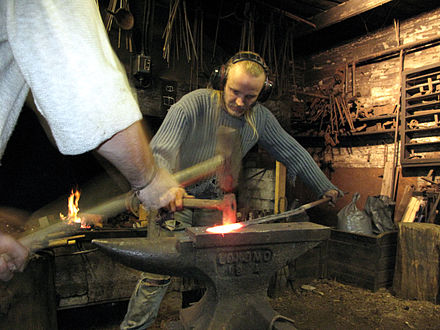 A blacksmith working with a sledgehammer, assistant (striker) and Lokomo anvil in Finland 3 tourist helping artist blacksmith in finland.JPG