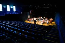 Empty blue seats and a small orchestra on a lighted stage, as seen from the rear of an auditorium