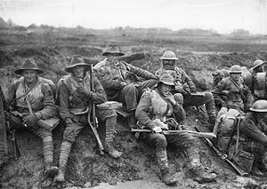 "Black and white photo of six men wearing military uniform seated on a muddy slope in France, December 1916. Unidentified members of the Australian 5th Division, enjoying a ""smoko"" near Mametz, on the Somme. Some are wearing slouch hats, steel helmets, sheepskin jackets and woollen gloves, demonstrating both the variety of official battledress, and how it was modified and augmented, for local conditions."