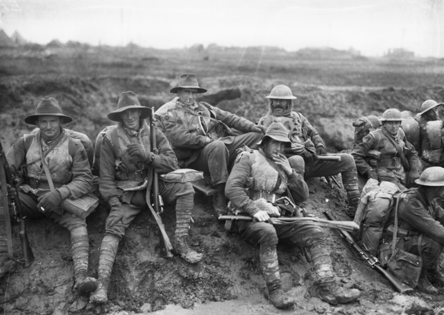 Black and white photo of six men wearing military uniform seated on a muddy slope