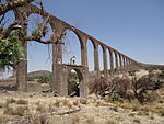 A tall, arched aqueduct in an arid landscape