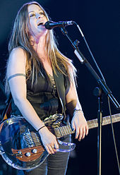 A Caucasian female with light colored hair leaning her head back while singing into a microphone. She is wearing a sleeveless green shirt with dark grey pants and has a guitar strapped around her.