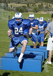 A halfback leads fellow backs through an agility drill at the Air Force Academy