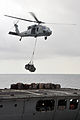 An MH-60 Seahawk helicopter transfer supplies from the fleet replenishment oiler USNS Rappahannock (T-AO 204) to the amphibious assault ship USS Boxer (LHD 4) during a replenishment at sea operation in 110317-N-ZS026-104.jpg