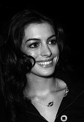 Anne Hathaway is smilin to her right in the black-and-white picture.