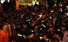 A tightly-bundled group of police officers in riot gear assembled in Jackson Road