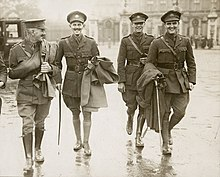 a group of four males in uniform walking along a street