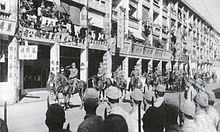 Japanske tropper går ind i Hongkong og marcherer på Queen's Road, under ledelse af generalløjtnant Takashi Sakai og viceadmiral Masaichi Niimi i december 1941, efter den britiske overgivelse.