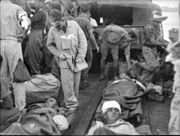 Wounded men lie on stretchers on the deck of a landing craft covered by blankets. Others are tending the wounded.