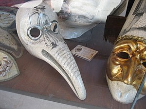 "Plague doctor costume - A beaked Venetian carnival mask with the inscription Medico della Peste (""Plague doctor"") beneath the right eye"