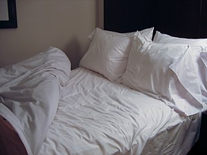 Bed made with white bed linen. Four fluffy pil...