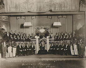 Group photo on a theatre stage of formally dressed men standing in three rows, one woman with small group at centre. The blackfaced end men are costumed.