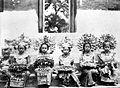 COLLECTIE TROPENMUSEUM Fraai aangeklede tempelmeisjes die sirih aanbieden voor de tempelpoort TMnr 10005112.jpg