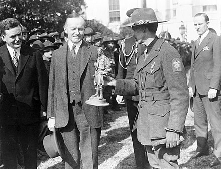 U.S. President Calvin Coolidge greeting 1500 Boy Scouts making an annual trip to the Capitol, 1927 Calvin Coolidge receiving statue of Boy Scout outside the White House 1927.jpg