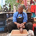 Carver sanding an elephant in water at green market square cape town.jpg