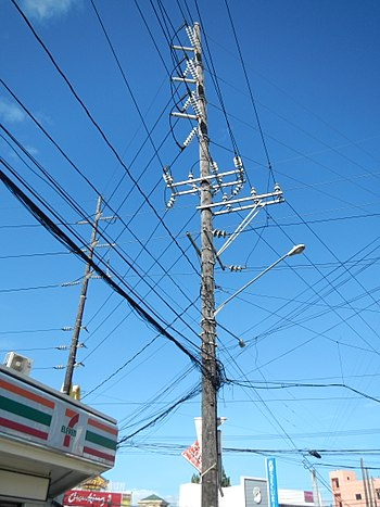 A 115 kV subtransmission line in the Philippines, along with 20 kV distribution lines and a street light, all mounted in a wood subtransmission pole Cavite, Batangas jf0557 11.jpg