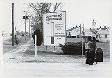 Two women walk past a large sign in Vietnamese and English at an army base
