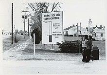 Deux femmes passent devant un grand panneau en vietnamien et en anglais sur une base militaire