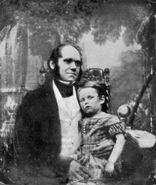 Darwin in de dertig, met zijn zoon gekleed in een jurk zittend op zijn knie.