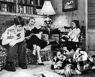 Perry Como - The Comos at home c. 1955. On the sofa are his older son Ronnie and wife Roselle. In the chair with her doll is his daughter, Terri, and reading on the floor are son David and his Dad.