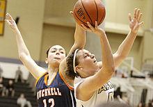Une joueuse posant la main sur le ballon tenu par une autre joueuse pour l'empêcher de tirer.