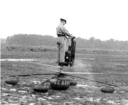 An Army officer in khakis and cap stands aboard a strange flying machine with twin rotors beneath his feet, running up on the ground, performing pre-flight checks.