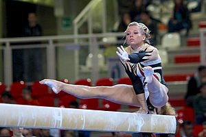 Balance beam - Dorina Böczögő performing a one arm press hold during her mount, 2012.