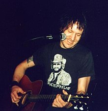A man performing live with an acoustic guitar. In front of him sits a microphone.