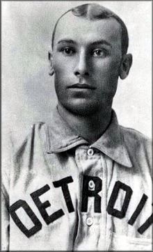 "A man wearing a baseball jersey with a with ""Detroit"" written across the chest."