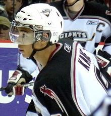 "A black, teenage hockey player as seen from the side, cut off below the shoulders. He is looking towards the left intently during a game. He wears a white, visored helmet and a white, black and red jersey with ""Kane"" written on his upper back and a maple leaf on his upper arm."
