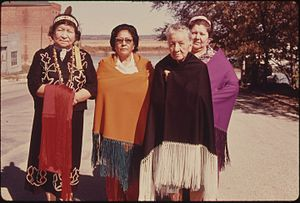 FOUR WOMEN OF THE IOWA INDIAN TRIBE ARE SHOWN WEARING A MODERN VERSION OF THEIR COSTUMES ON THE MAIN STREET OF WHITE... - NARA - 557158.jpg