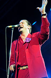 A man in a red suit standing in front of a microphone stand, with one arm raised