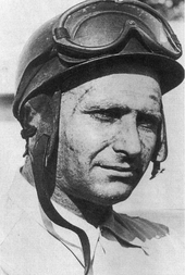 The head and shoulders of a man in his 40's, wearing a helmet with goggles placed on top of it, and a lightly-coloured shirt