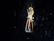 A blond female performer floating in a silver platform above the audience. She is wearing a silver outfit and a white mask.