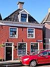 foto van Pand met verdieping met negenruitsvensters onder zadeldak met voorschild met dakkapel en topschoorsteen met bord