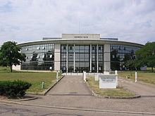 Un hormigón blanco y vidrio, edificio de frente curvo con un camino de entrada separados por una mediana que conduce a ella
