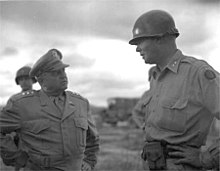 A tall man in military uniform converses with a shorter man in uniform