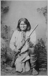 Geronimo (Goyathlay), a Chiricahua Apache, full-length, kneeling with rifle, 1887 - NARA - 530880.tif