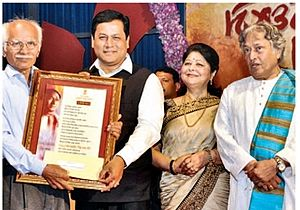 Bishnu Prasad Rabha - Hon'ble Chief MInister of Assam, along with Ustad Amjad Ali Khan (Right), presenting the Bishnu Rabha Award 2016 to Veteran Artist Girish Chandra Borah