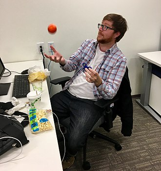 Goofing off - A man goofing off at work, playing with a fidget spinner and a ball
