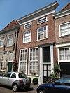 foto van Huis met schilddak en lijstgevel in schoon-werk, kroonlijst met tandlijst, attiekvormige zolderverdieping, versierde deuromlijsting. Nog geheel woonhuisvorm