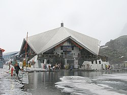 A stone building is surrounded by partially frozen ponds. Pilgrims can be seen on the paths