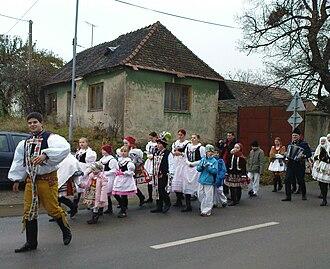 "Kermesse (festival) - Kermesse in the Moravian Slovak village of Bohuslavice u Kyjova (Czech Republic, 2009) - a procession through the village is led by a ""stárek"" (festival leader) wearing a national costume, yellow deer-skin trousers"