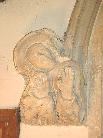 Horspath - St Giles' parish church: 15th century carved stone figure of a man expressing amazement, forming the left label stop of the tower arch