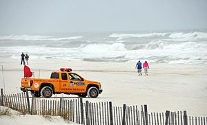 A Pensacola Beach Lifeguard pickup truck parked at a beach with rough seas. Two people are walking close to the water's edge in the background and two more are walking towards the water in the center of the image.