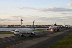Five jumbo airplanes wait in a line on a runway next to a small body of water. Behind them in the distance is the airport and control tower.
