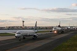 Cinco aviões jumbo esperar em uma linha em uma pista ao lado de um pequeno corpo de água.  Atrás deles na distância é o aeroporto e torre de controle.