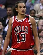 "A basketball player, wearing a red jersey with the word ""BULLS"" and the number 13 on the front, is standing on a basketball court."