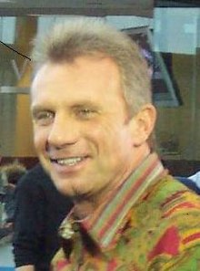 A man smiling and wearing a green and red shirt.
