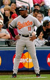 "A dark-skinned man in his mid-forties wearing a gray baseball uniform stands with arms akimbo. His uniform reads ""Orioles"" in orange script lettering across the chest, with a block ""11"" below it in orange, and is accompanied by a black batting helmet."